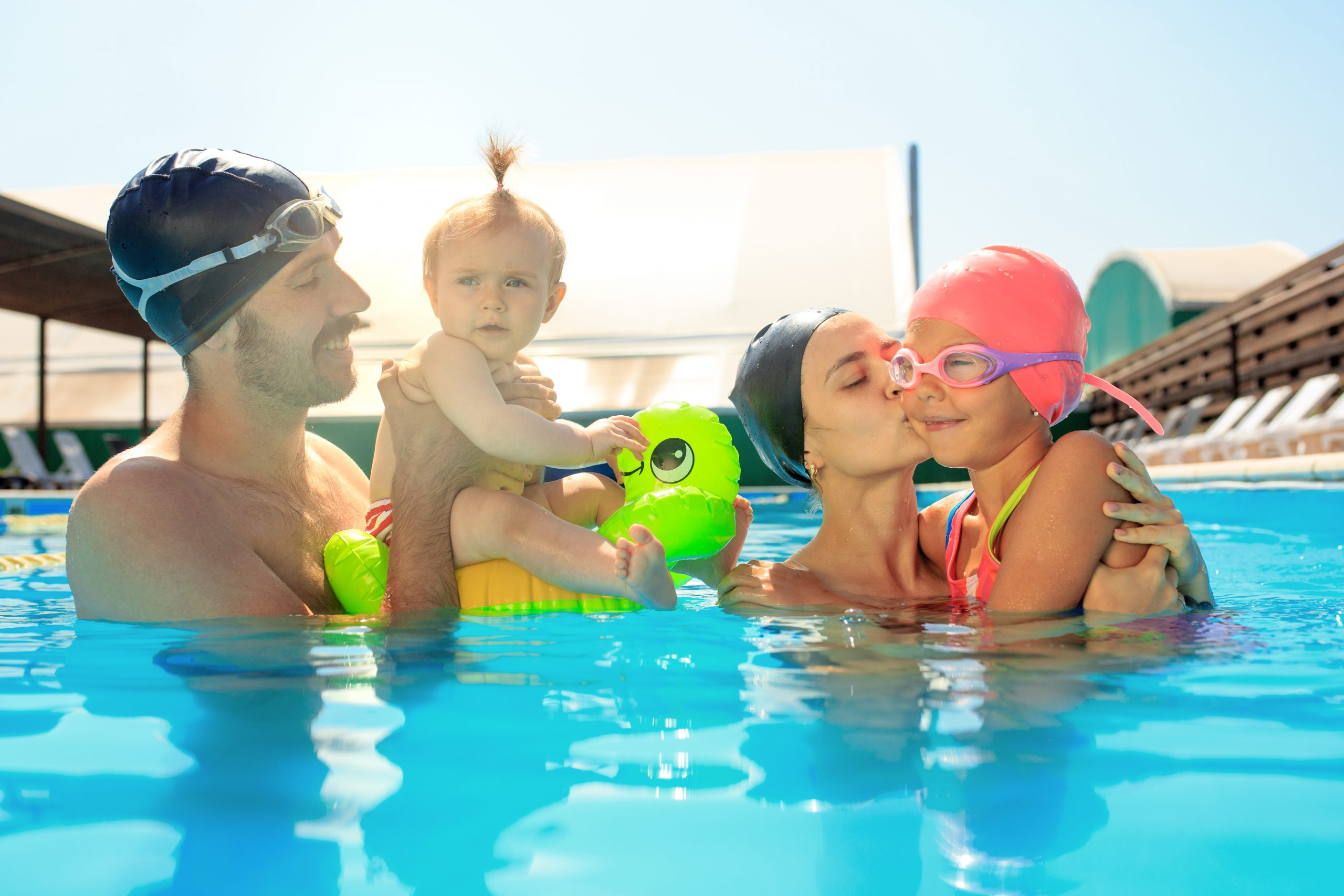 Happy family having fun by the swimming pool. Pool, leisure, swimming, summer, recreation, healthy lifstyle concept